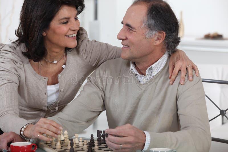 Pares que juegan a ajedrez fotos de archivo