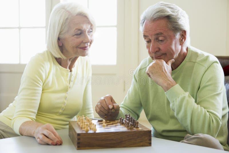 Pares que juegan a ajedrez en la sonrisa de la sala de estar fotografía de archivo libre de regalías