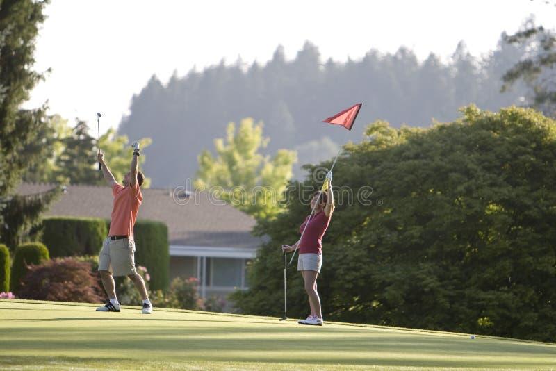 Pares que juegan al golf - horizontal imagenes de archivo
