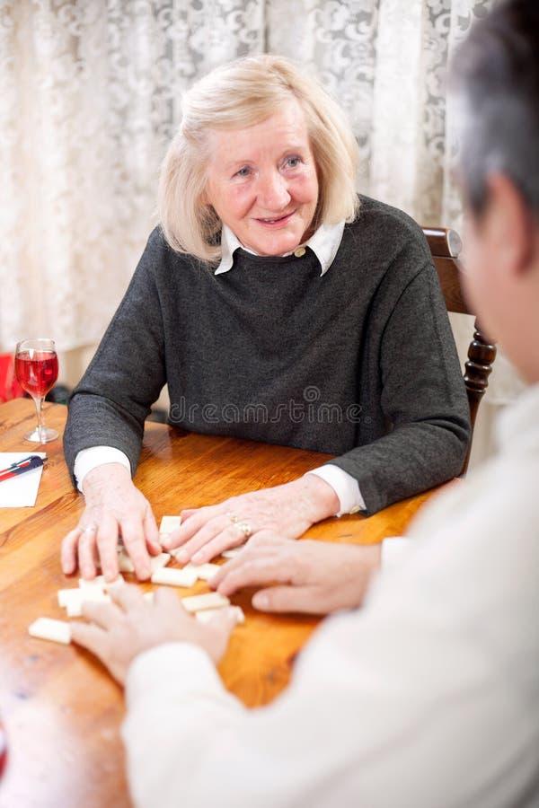 Pares que juegan dominós en la sonrisa de la sala de estar fotografía de archivo