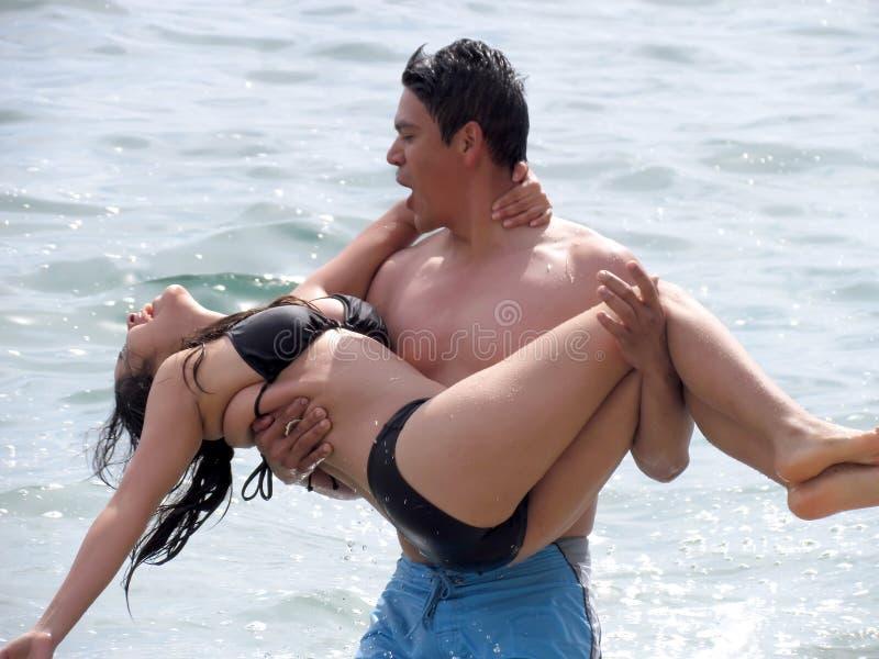 Pares que juegan en las ondas y la playa imagen de archivo libre de regalías