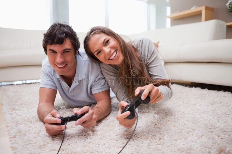 Pares que juegan a los juegos video en el suelo foto de archivo