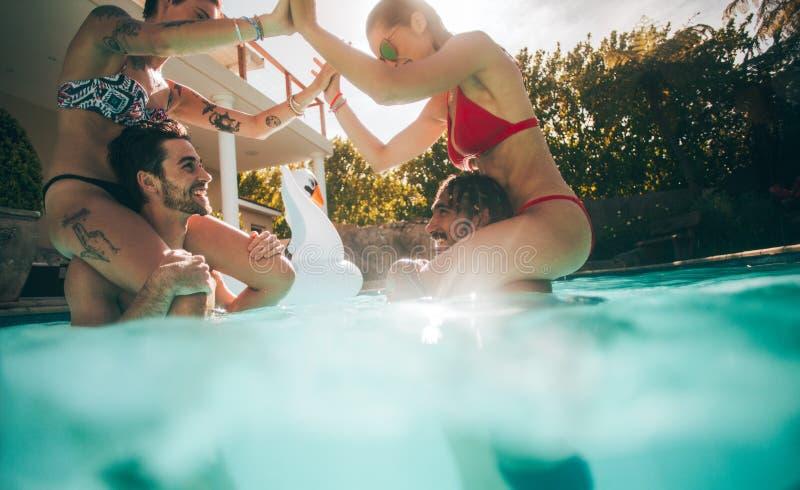 Pares que juegan y que gozan en una piscina foto de archivo libre de regalías