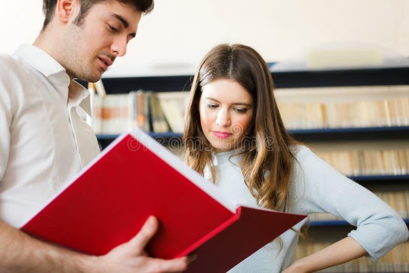 Pares que leen un libro en una biblioteca fotografía de archivo