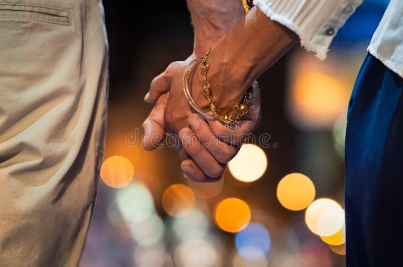 Pares que llevan a cabo la mano en la noche foto de archivo libre de regalías