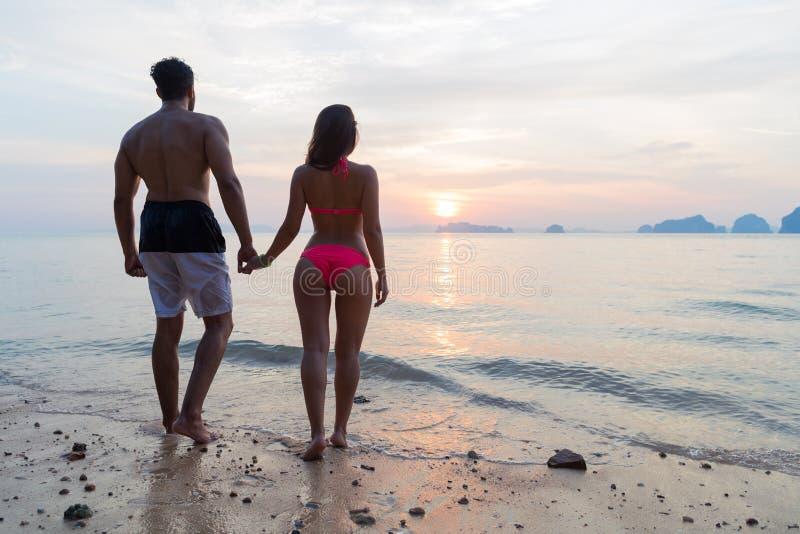 Pares que llevan a cabo las manos en la playa en la vista posterior de la parte posterior de la puesta del sol, el hombre turísti imagenes de archivo