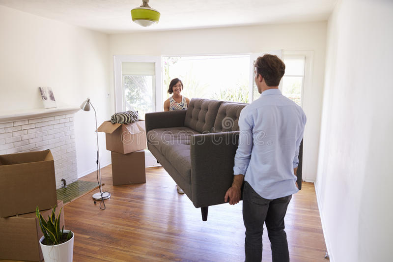 Pares que llevan el día móvil de Sofa Into New Home On imagen de archivo libre de regalías