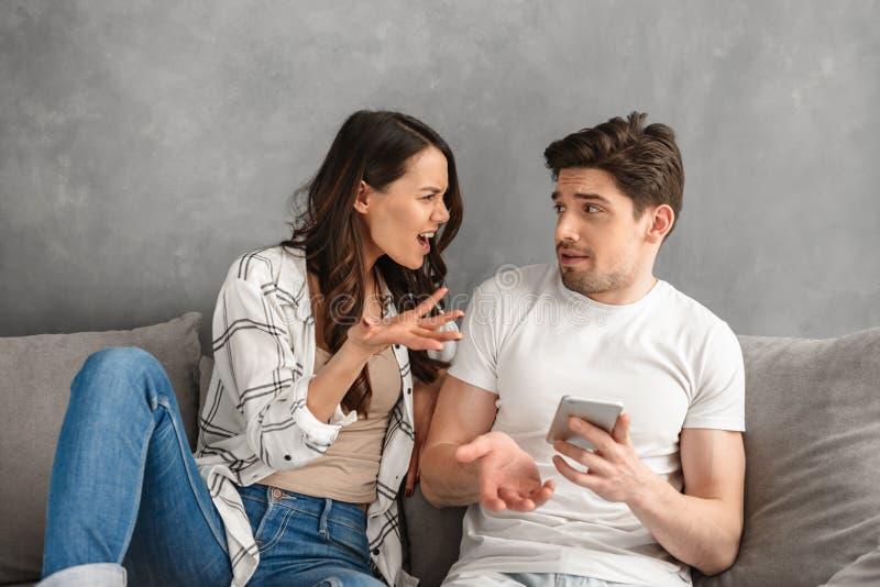 Pares que luchan que se sientan junto en el sofá en casa mientras que sho de la mujer imagen de archivo