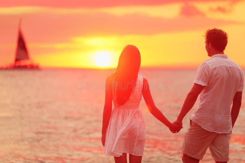 Pares que mantêm as mãos unidas no por do sol da praia fotografia de stock royalty free