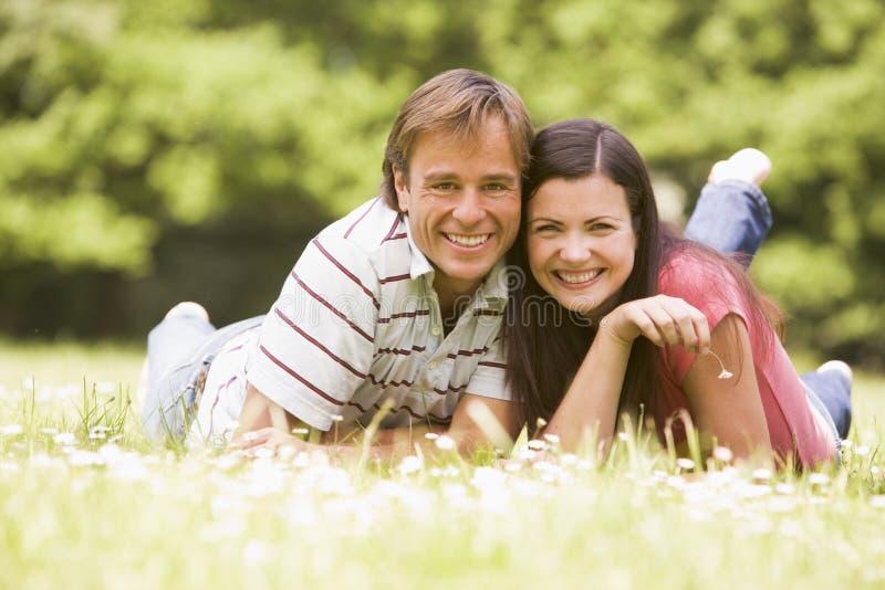 Pares que mienten al aire libre con la sonrisa de la flor imagen de archivo libre de regalías