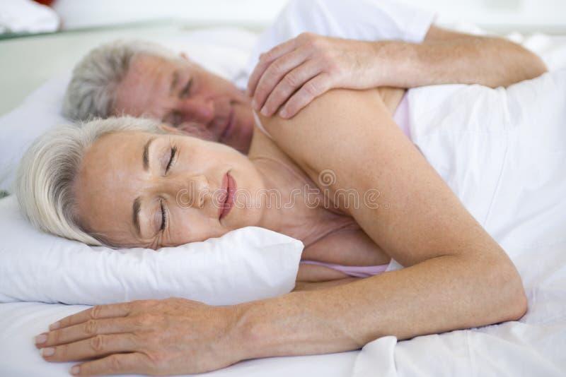 Pares que mienten en la cama junto que duerme imágenes de archivo libres de regalías