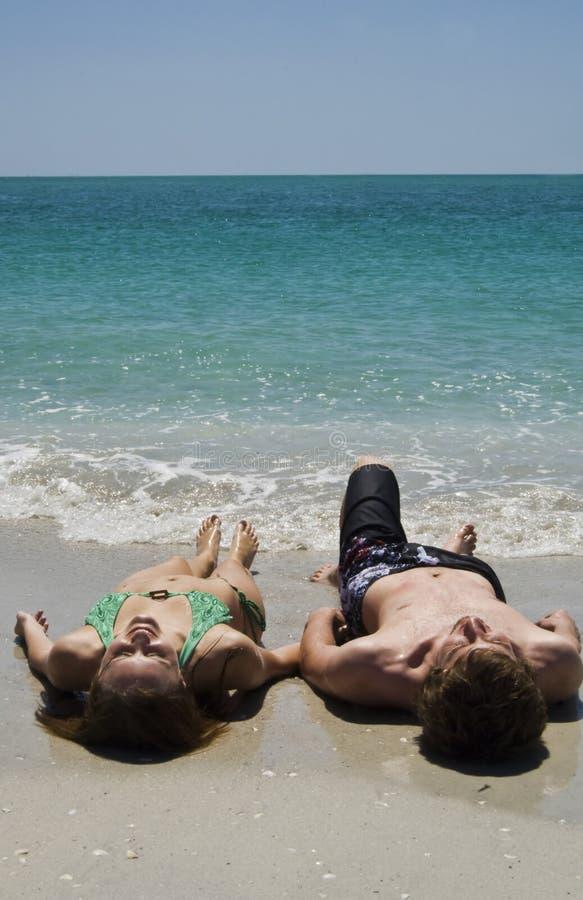 Pares que mienten en la playa foto de archivo libre de regalías
