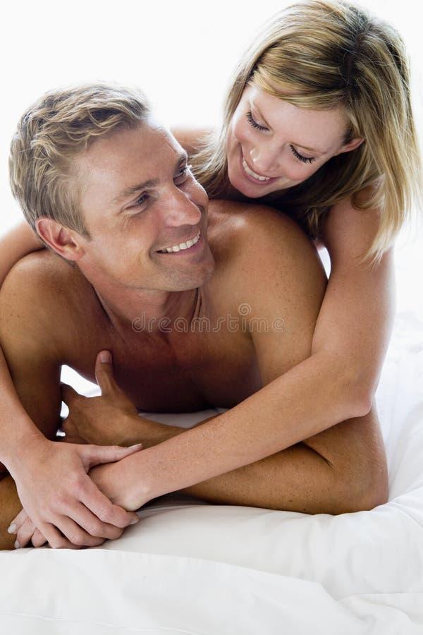 Pares que mienten en la sonrisa de la cama imagen de archivo libre de regalías