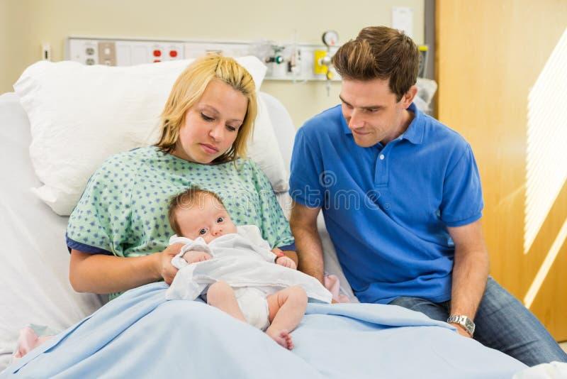 Pares que miran al bebé recién nacido en sitio de hospital foto de archivo libre de regalías