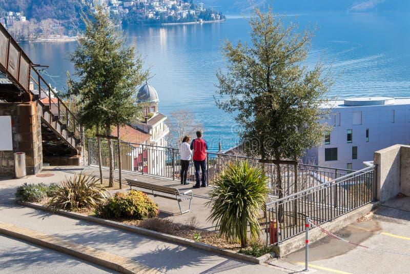 Pares que miran la vista asombrosa de la ciudad de Lugano, Suiza imagenes de archivo