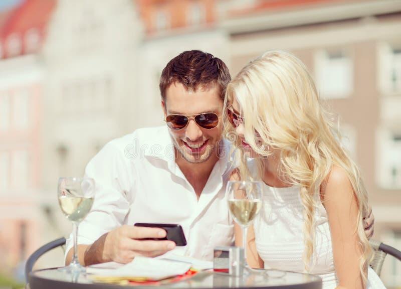 Pares que miran smartphone en café imagen de archivo