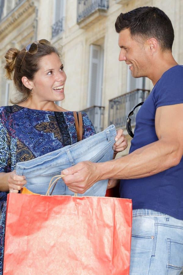 Pares que miran sus compras de la ropa foto de archivo