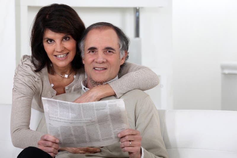 Pares que miran un periódico fotografía de archivo libre de regalías