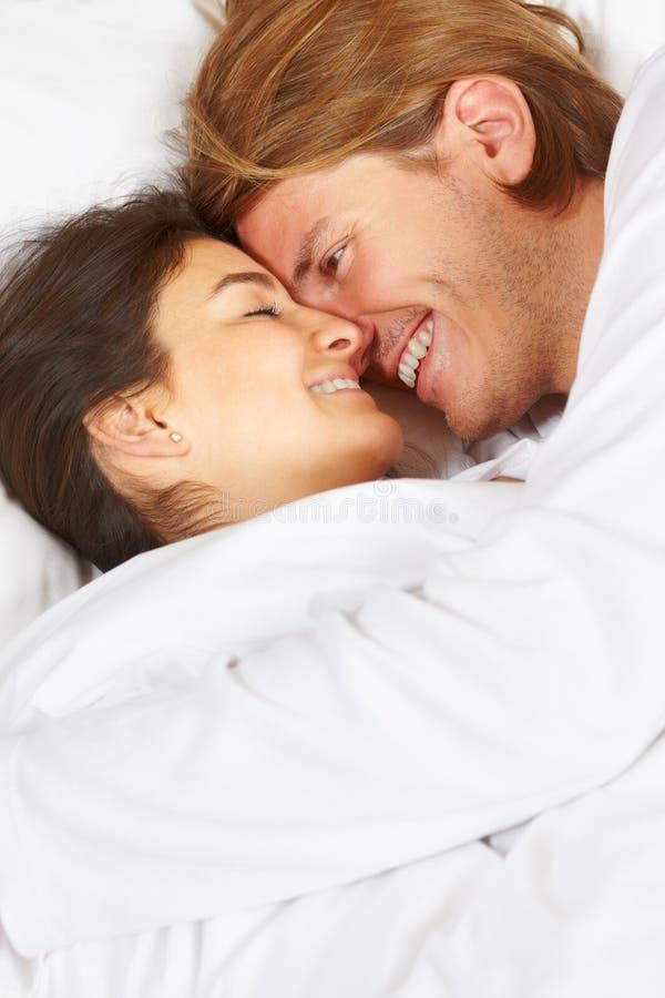 Pares que mostram o romance na cama imagem de stock royalty free