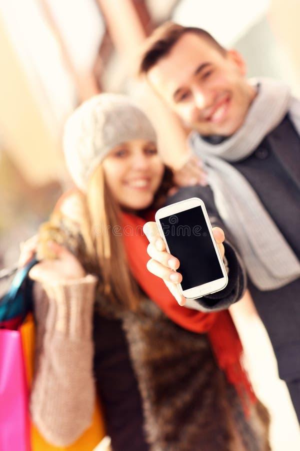 Pares que muestran smartphone mientras que hace compras foto de archivo