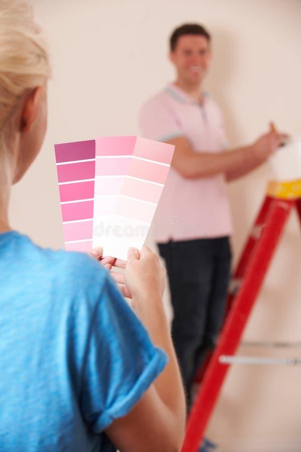 Pares que olham amostras de folha da pintura na casa nova fotografia de stock