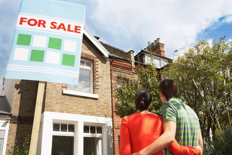 Pares que olham a casa nova com para sinal da venda imagens de stock