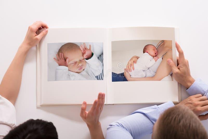 Pares que olham o álbum de fotografias do bebê fotografia de stock royalty free