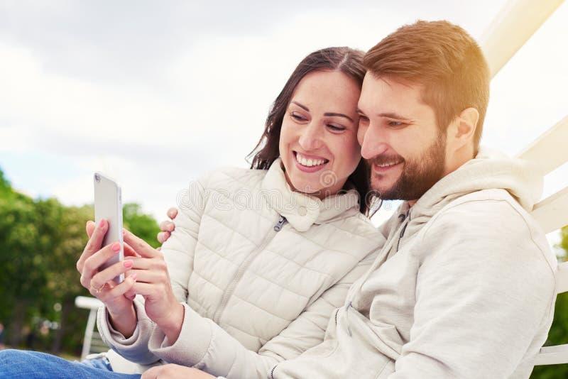 Pares que olham o telefone celular fotografia de stock royalty free