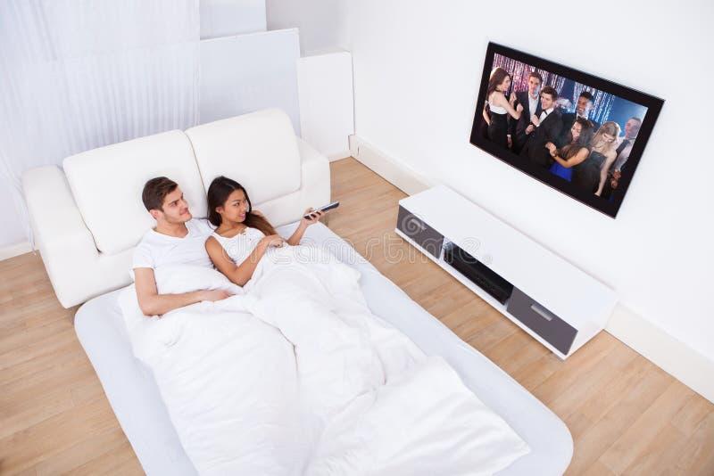 Pares que olham a tevê na cama em casa imagem de stock royalty free