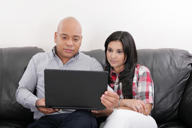 Pares que pensam e que olham um laptop fotografia de stock