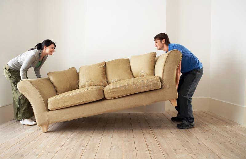 Pares que ponen el nuevo hogar de Sofa In Living Room Of fotografía de archivo
