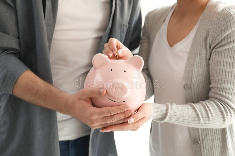 Pares que ponen la moneda en la hucha, primer Concepto de los ahorros del dinero imágenes de archivo libres de regalías