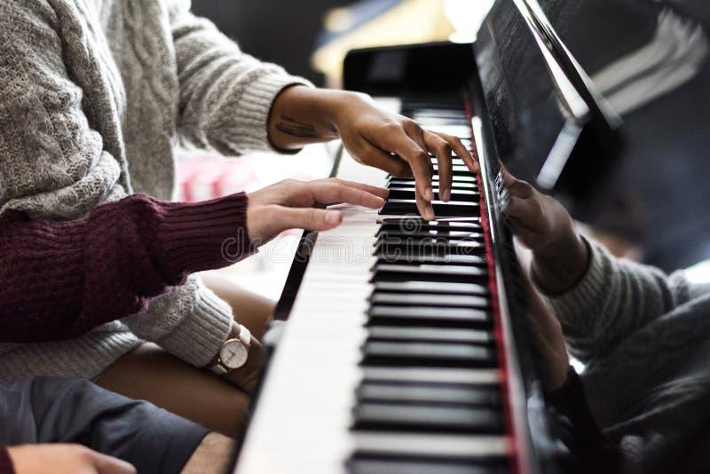 Pares que practican en un piano junto foto de archivo