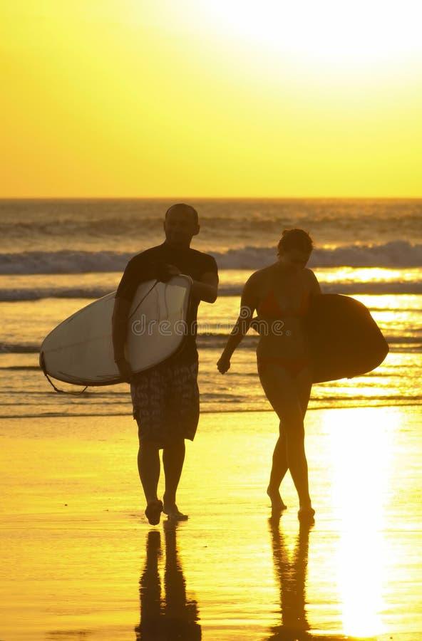 Pares que practican surf en la playa del kuta imágenes de archivo libres de regalías