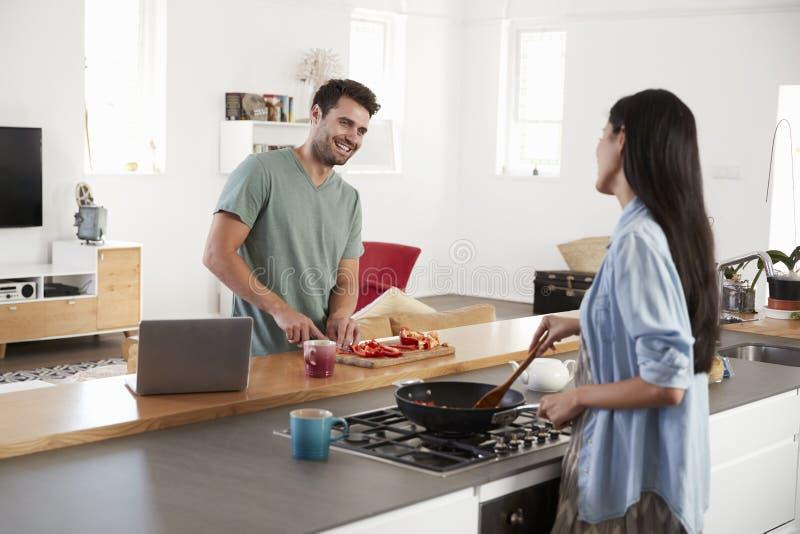 Pares que preparam a refeição junto na cozinha moderna fotos de stock royalty free
