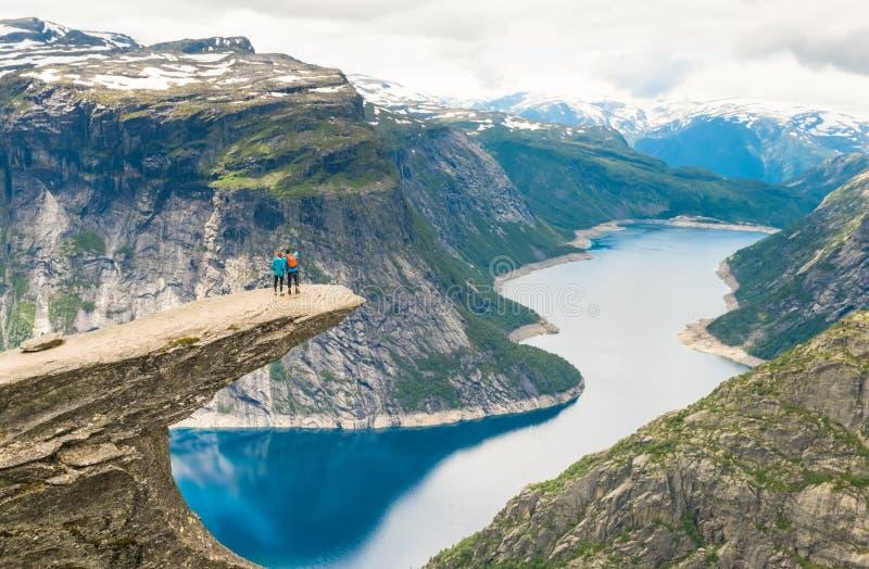 Pares que presentan en Trolltunga Noruega fotografía de archivo