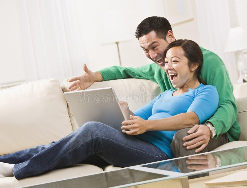 Pares que ríen mientras que mira una computadora portátil junto foto de archivo