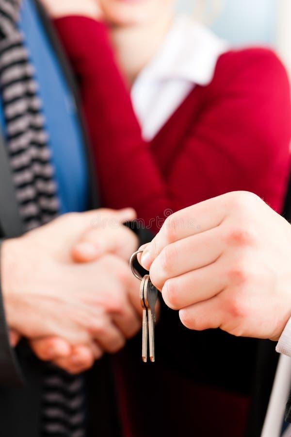 Pares que recebem chaves do corretor de bens imobiliários fotos de stock royalty free