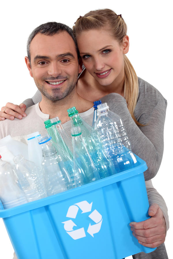 Pares que reciclam garrafas plásticas fotografia de stock