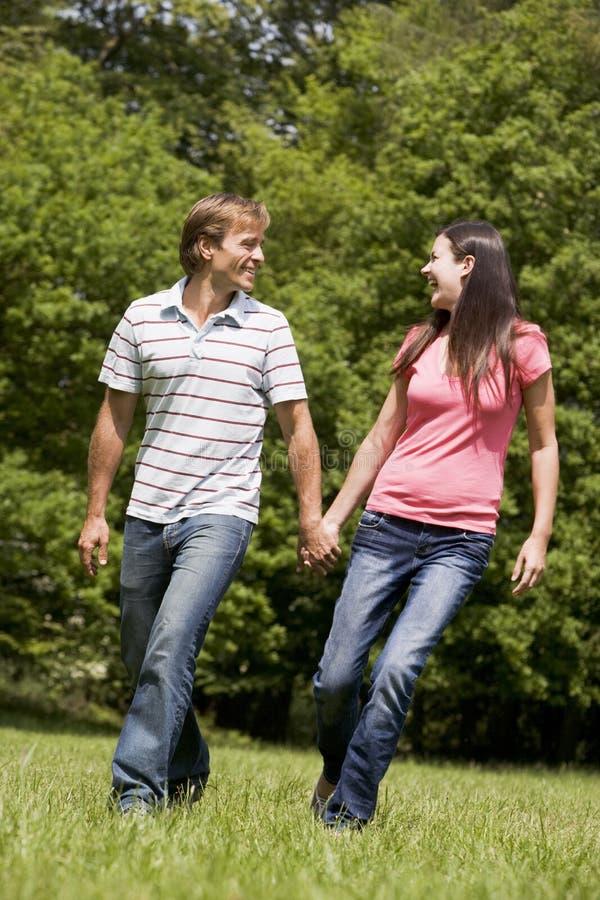 Pares que recorren al aire libre celebrando la sonrisa de las manos fotografía de archivo