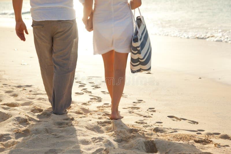 Pares que recorren en la playa fotografía de archivo libre de regalías