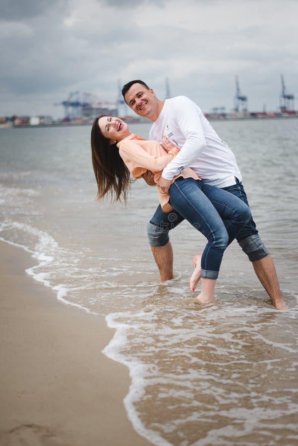 Pares que recorren por Heron Hombre y mujer en la arena fotos de archivo