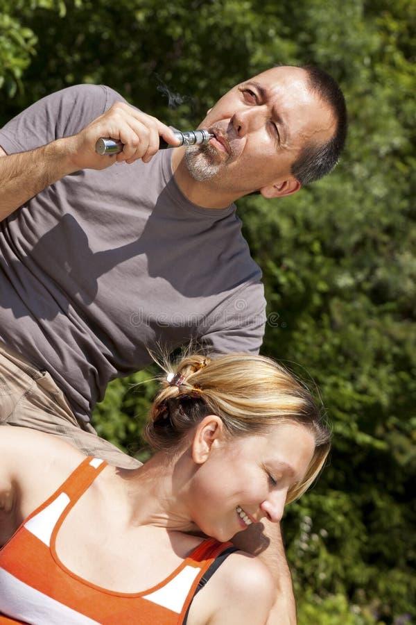 Pares que relaxam com e-cigarro imagens de stock