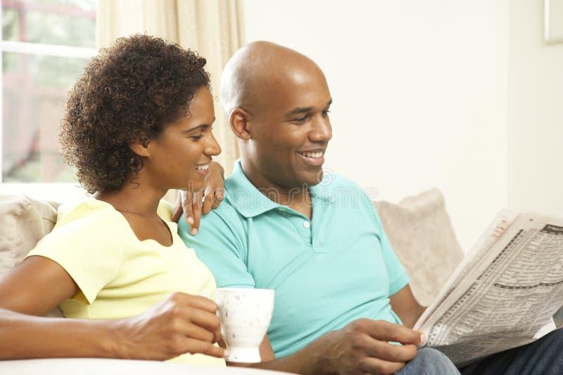 Pares que relaxam em casa com jornal imagens de stock