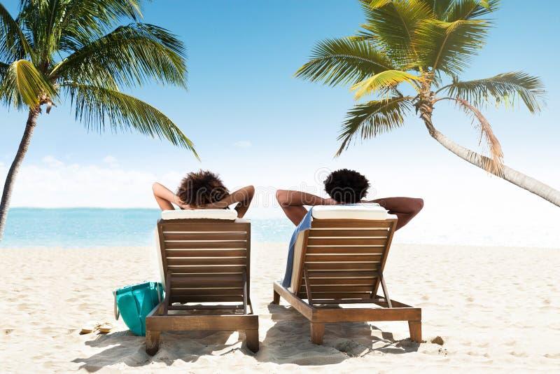 Pares que relaxam na cadeira de plataforma fotografia de stock