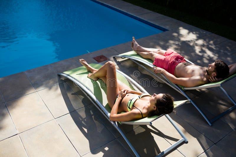 Pares que relaxam na cadeira de sala de estar na piscina imagens de stock royalty free