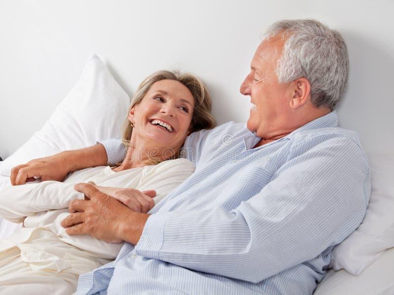 Pares que relaxam na cama imagens de stock royalty free