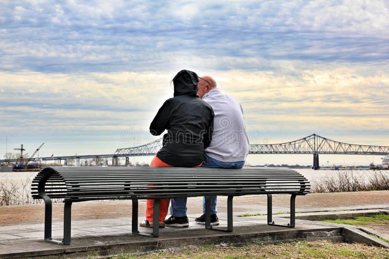 Pares que relaxam na frente da ponte do rio Mississípi no tempo do por do sol fotos de stock