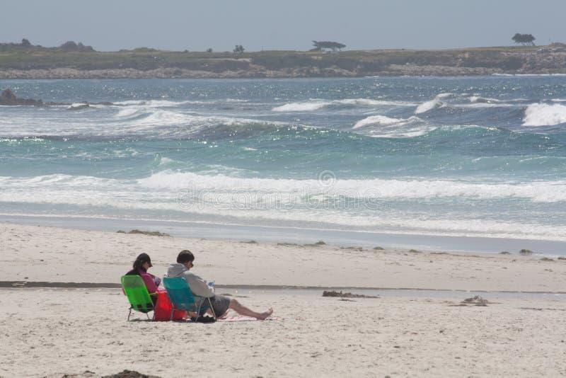 Pares que relaxam na praia imagens de stock