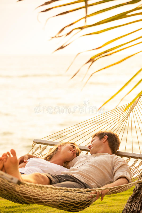 Pares que relaxam na rede tropical fotos de stock royalty free